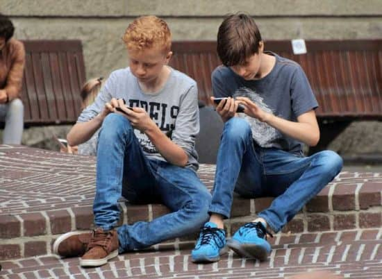 Two young boys looking at phones