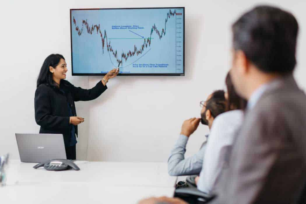 woman at work meeting pointing to a chart on the wall