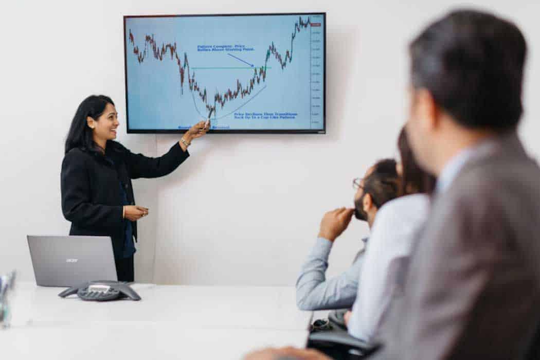 femme pointant a l'écran dans une réunion de bureau