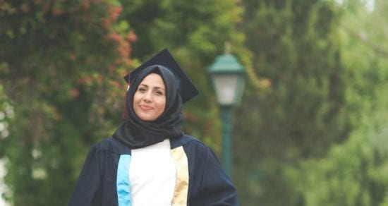 A woman graduate in hijab in front of trees