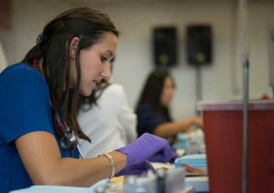 agent de santé féminin avec des gants violets
