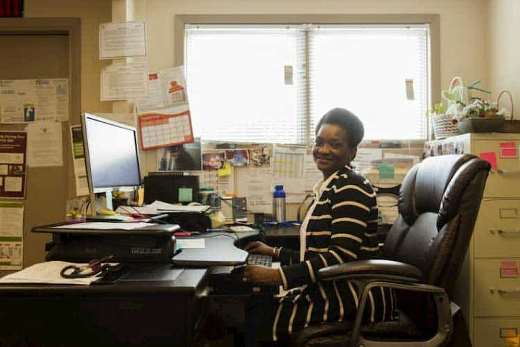 woman in a striped sweater sitting at computer