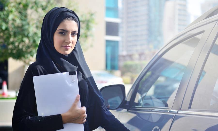 mujer vestida de negro con papeles en vehículo