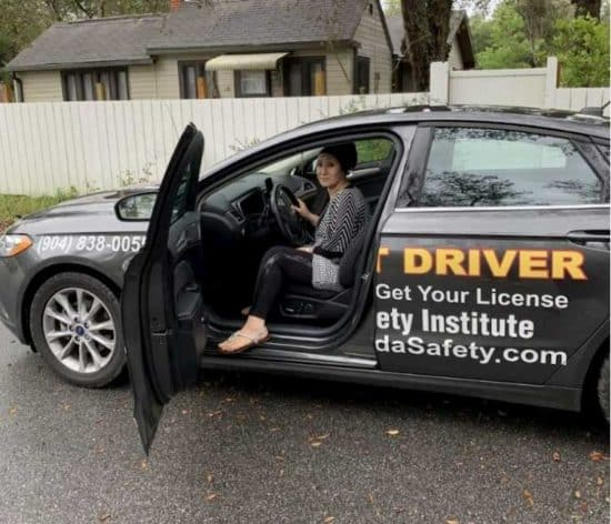 woman in the driver's seat of a black car