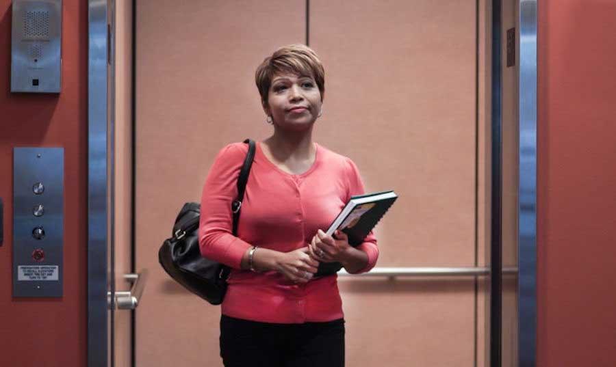 woman holding books standing in elevator doorway