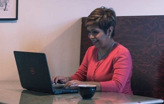 woman in red shirt typing on a laptop at a cafe table