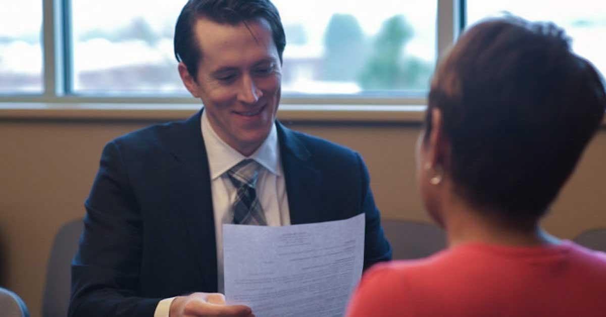 mujer mostrando currículum al entrevistador