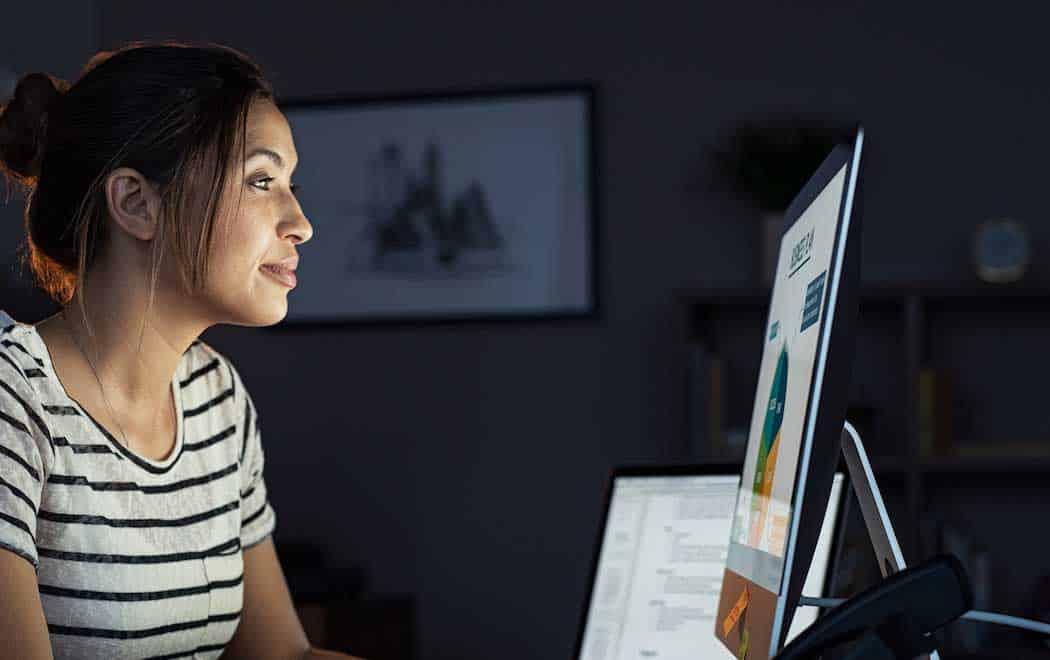 una mujer en una camiseta a rayas mirando la pantalla de una computadora