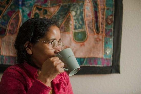امرأة ترتدي نظارات تشرب من كوب
