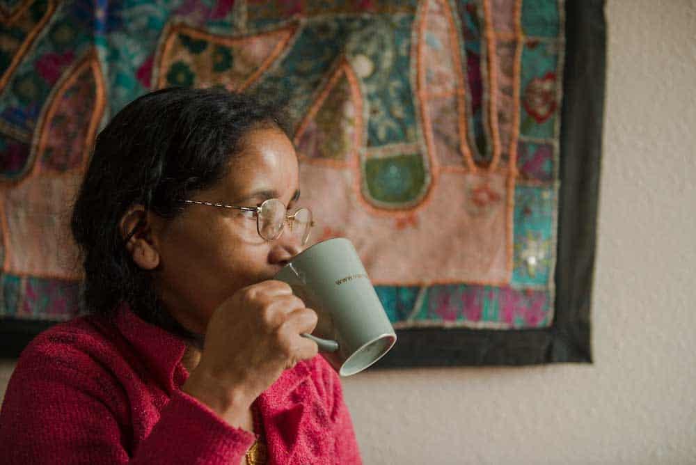 femme portant des lunettes buvant dans une tasse