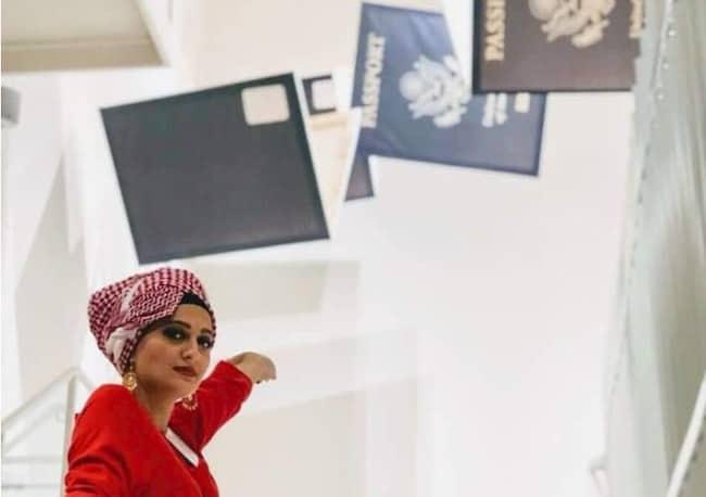 Basma Alawee in front of a visa display
