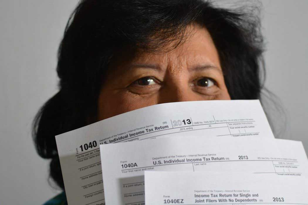 A woman with tax forms in front of her face