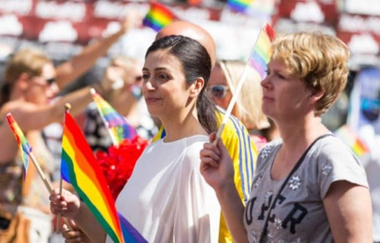 Two women at Pride parade carrying rainbow flags