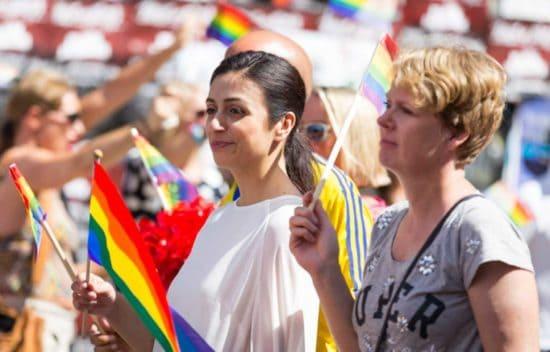 امرأتان في موكب تحملان أعلام قوس قزح