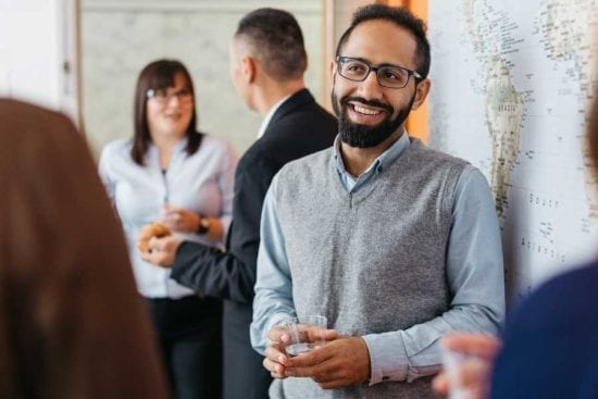 man holding a glass at work networking event