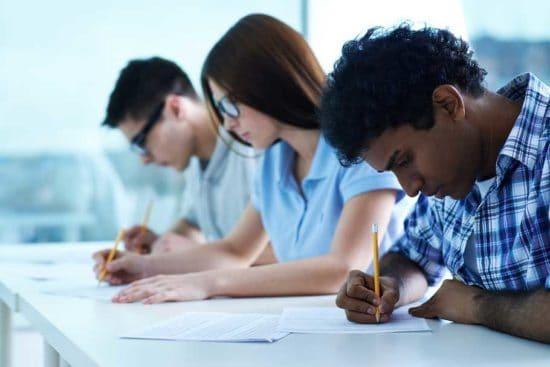 Tres jóvenes estudiantes adultos escribiendo en una mesa de clase