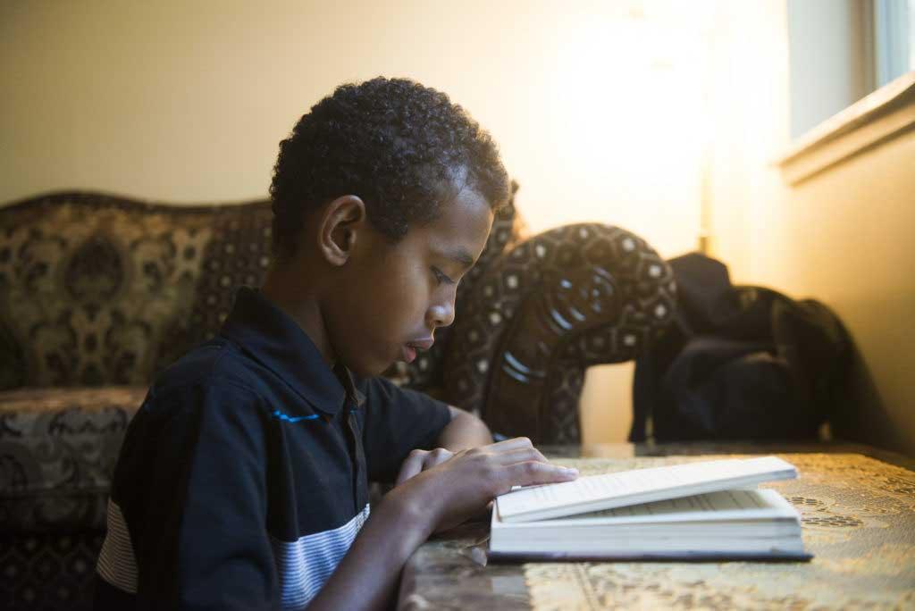 صبي صغير قراءة الكتاب في المنزل