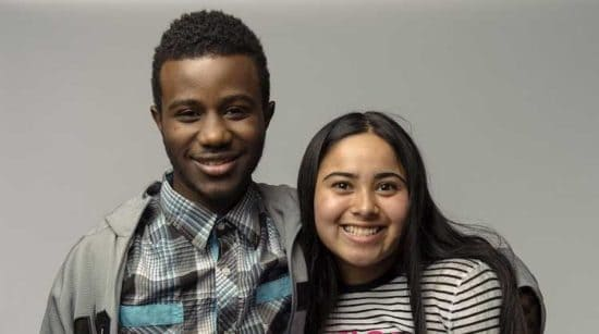 young man and woman side by side hugging and smiling at camera