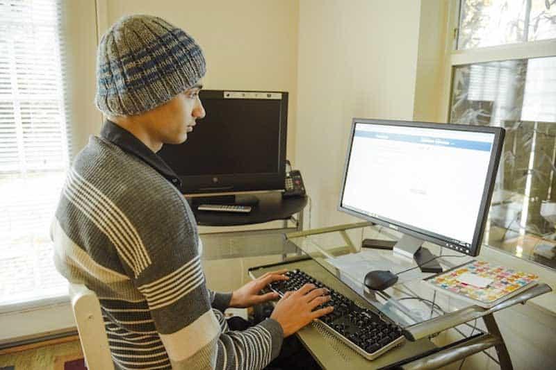 garçon portant chapeau assis à l'ordinateur