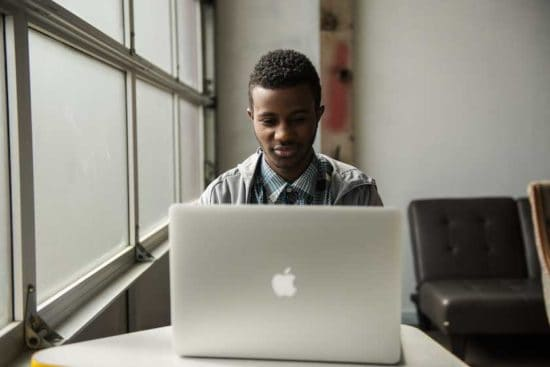 young man with laptop by a window