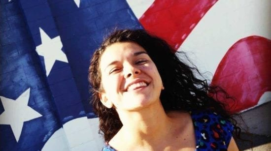 young smiling woman in front of us flag