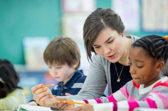 a young woman teacher helping little girl