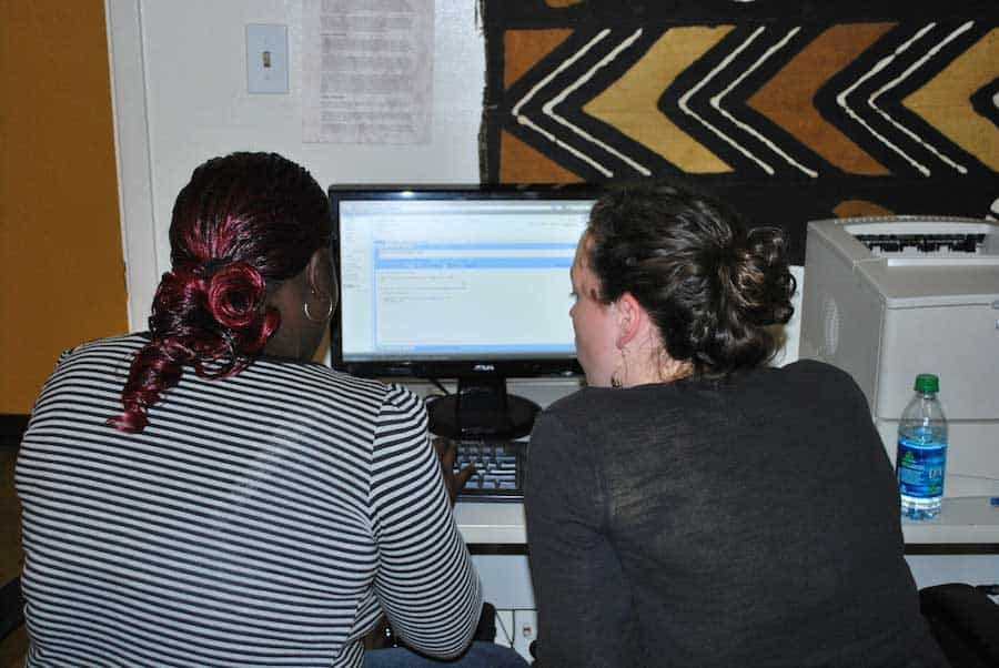 back view of two young women sitting at a computer