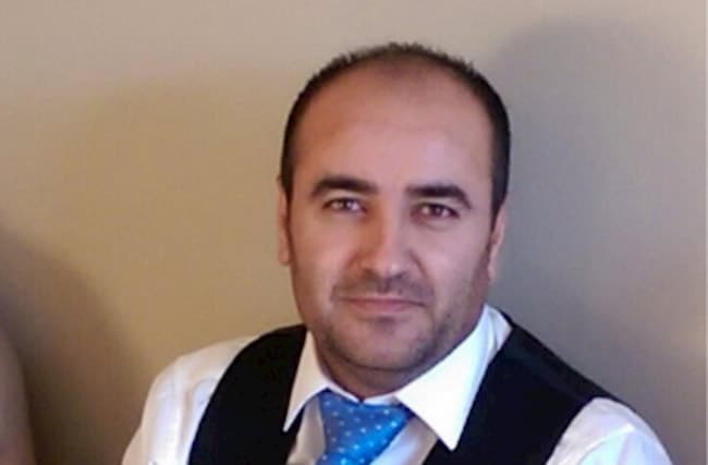 Naser in suit looking at the camera