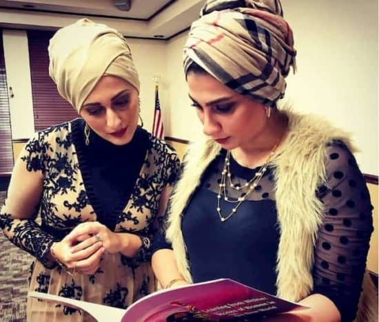 Basma Alawee and her sister Marwah Alobaidi looking at a book
