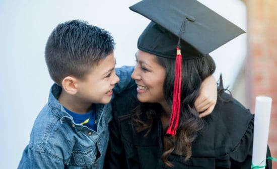 graduate woman hugging child