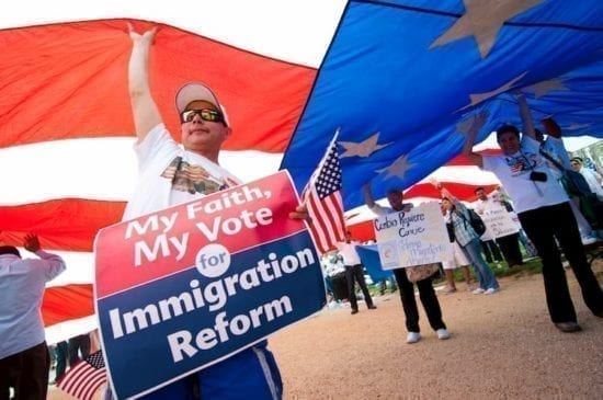 immigrant activist with giant US flag