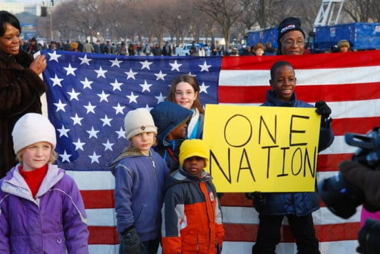 adults and kids holding one nation sign and flag