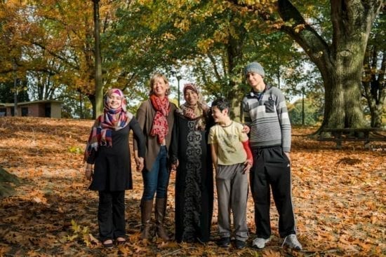 refugee family and volunteer smiling in park