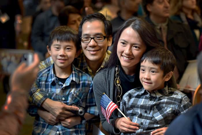 young smiling family holding small flag
