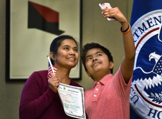 mom and son selfie with naturalization certificate