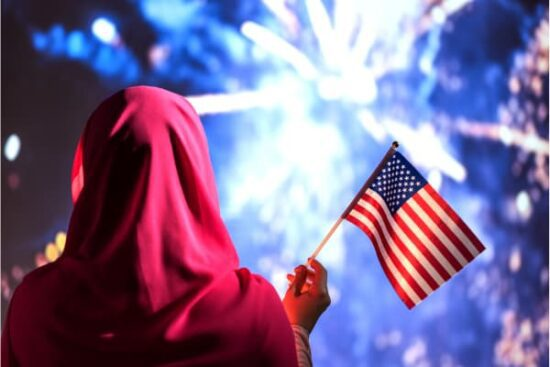 Muslim woman in a scarf holding American flag during fireworks at night